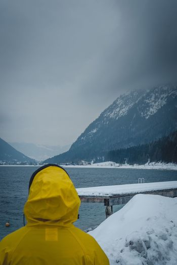 Watching Fjords Raincoat Yellow Traveling Travel Adventure EyeEmNewHere Norway Fjørd Fjord Snow Winter Cold Temperature Mountain Weather One Person Nature Beauty In Nature Tranquility Rear View Scenics Frozen Real People Warm Clothing Standing Sky Outdoors Day Mountain Range Women