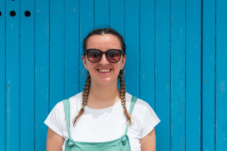 Portrait of a smiling young woman standing against blue wall