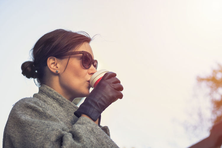 Portrait of young woman holding eyeglasses against clear sky