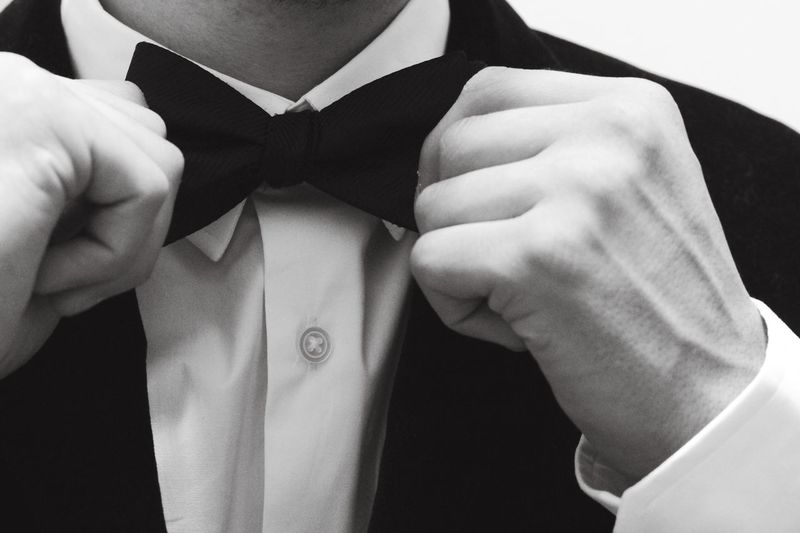 Close-up of man adjusting his bow tie