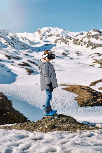 Rear view of person standing on snowcapped mountain