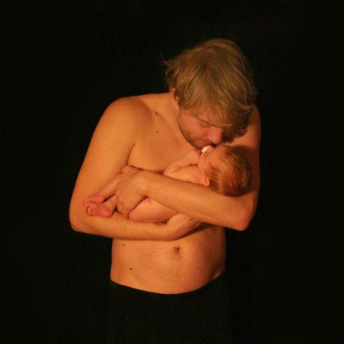 Shirtless man holding newborn baby against black background