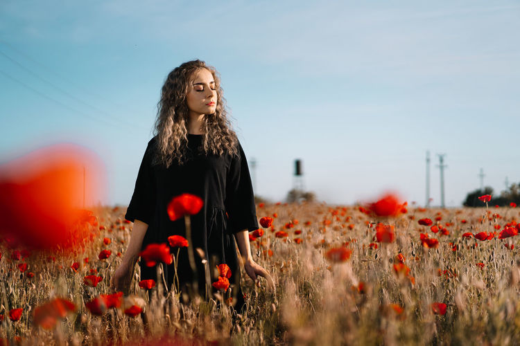 Beautiful young woman standing by poppy flowers on field against sky