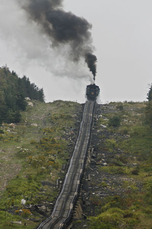 Steam Train of Mount Washington Cog Railway is pusing up Coach to the summit at good weather conditions Blue Sky White Clouds Bretton Woods Mount Washington Cog Railway Narrow Gauge Railway New Hampshire, USA Smoke Air Pollution Day Emitting Environment Environmental Damage Environmental Issues Factory Fuel And Power Generation Industry Land Nature No People Outdoors Plant Pollution Sky Smoke Smoke - Physical Structure Smoke Stack Summit Tree