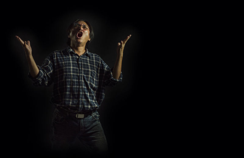 Portrait of a man shouting for victory. Or success in the concept of expressing one's emotions. Black Background One Person Studio Shot Indoors  Casual Clothing Adult Standing Looking Three Quarter Length Human Arm Looking Away Men Emotion Limb Arms Raised Copy Space Looking Up Human Limb Illuminated Dark Mouth Open Rolled-up Sleeves Contemplation