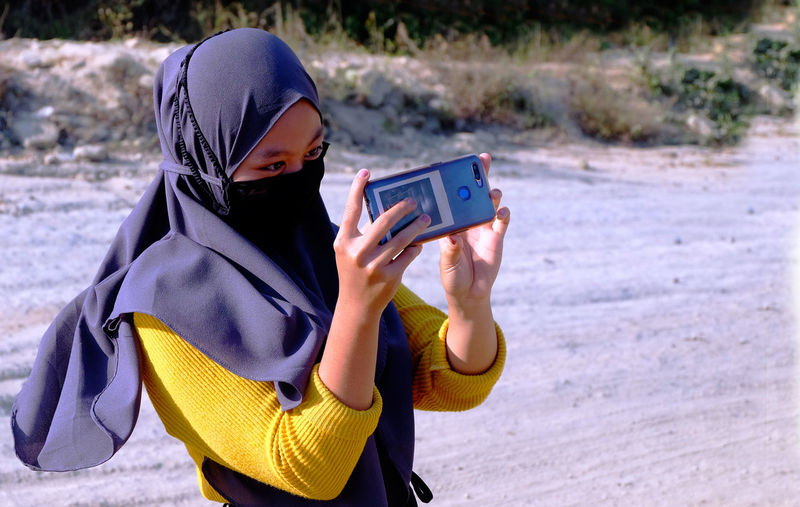 Woman  photographing with mobile phone wearing hijab