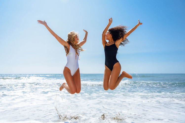Happy female friends jumping on shore at beach