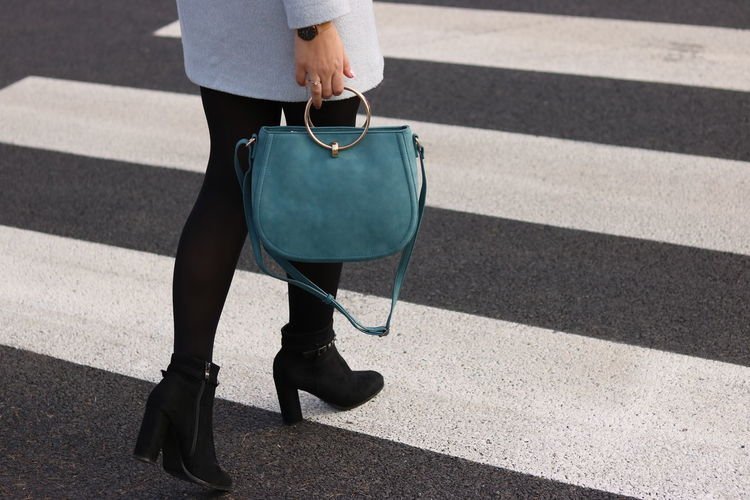 Low Section Of Woman Holding Purse While Crossing On Road