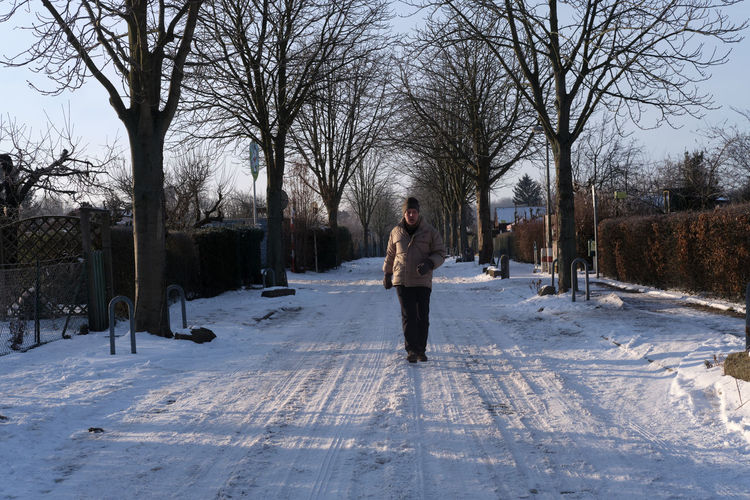 Man standing on snow covered footpath