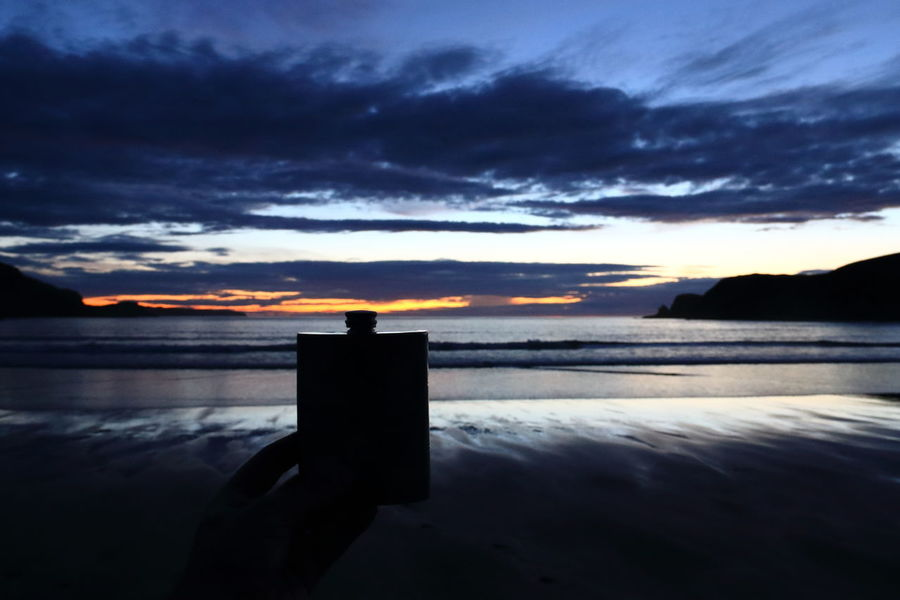 Beach dram. Coast Coastline Beauty In Nature Scotland Sea Beach Sand Sunset Sunset Silhouettes Hipflask Whisky Bettyhill Travel Destinations North Coast 500 Nc500 Silouette & Sky Sky Scenics Tranquility Darkness Dark Night Dusk Light Dram
