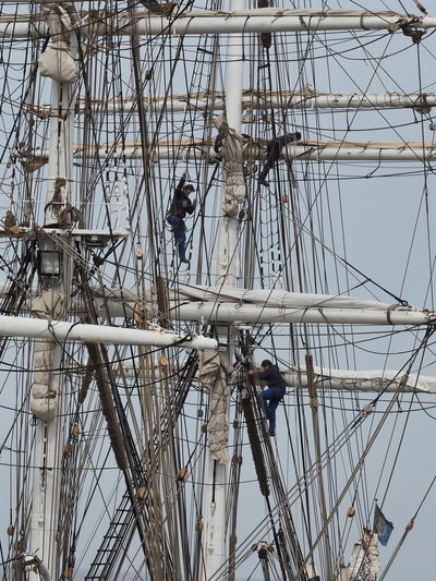 Low angle view of workers on ship against clear sky