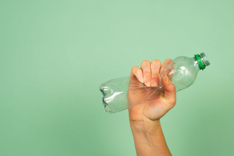 hand holding smashed memory plastic bottle against green background.  concept for recycling.