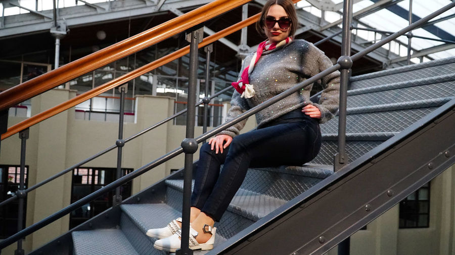 Railing Architecture Full Length Real People One Person Built Structure Steps And Staircases Staircase Casual Clothing Clothing Young Adult Lifestyles Leisure Activity Front View Day Women Adult Looking Away Outdoors Warm Clothing