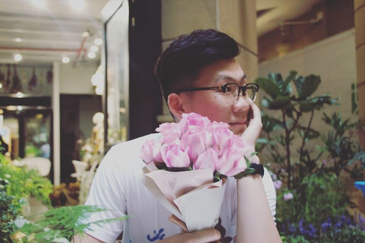 Thoughtful young man holding roses in flower shop