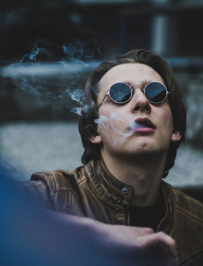 Close-up of man wearing sunglasses exhaling smoke