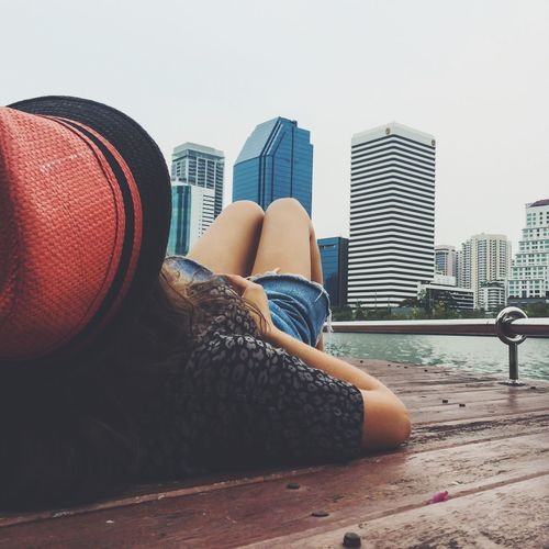 Woman lying on pier at river against buildings