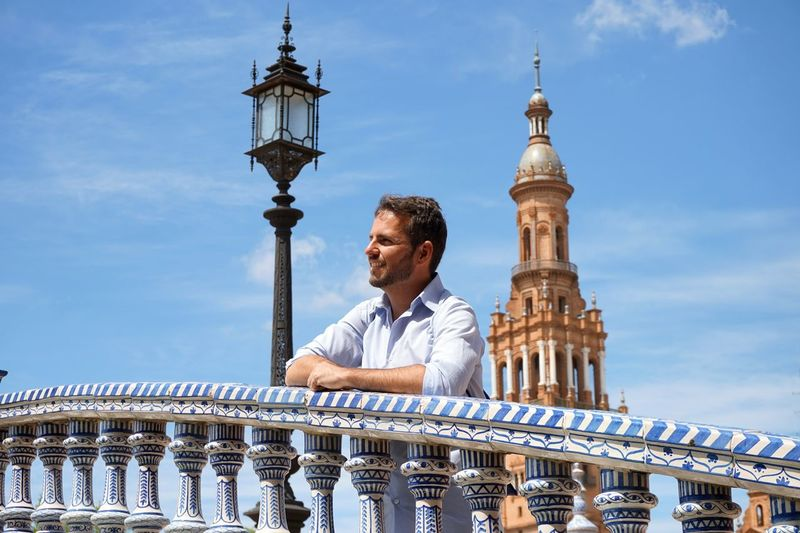 Man leaning on railing with historic tower in background against blue sky