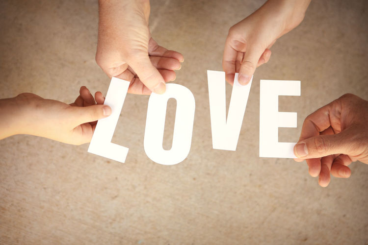 "Close-up of human hands holding the word ""love"""