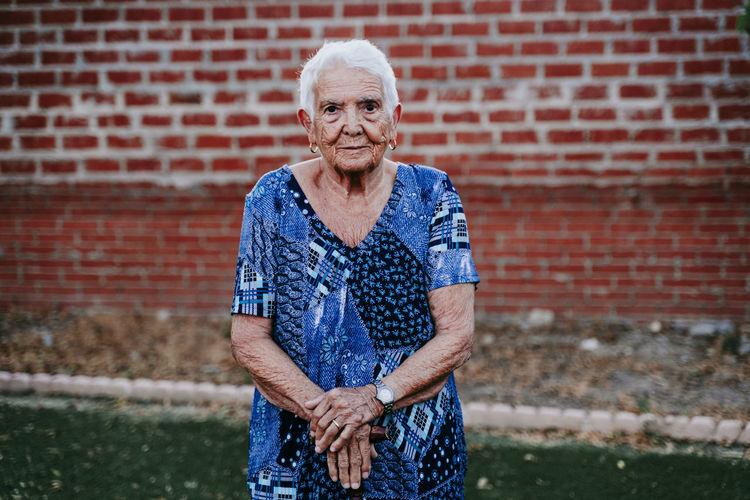 Portrait of woman standing against brick wall