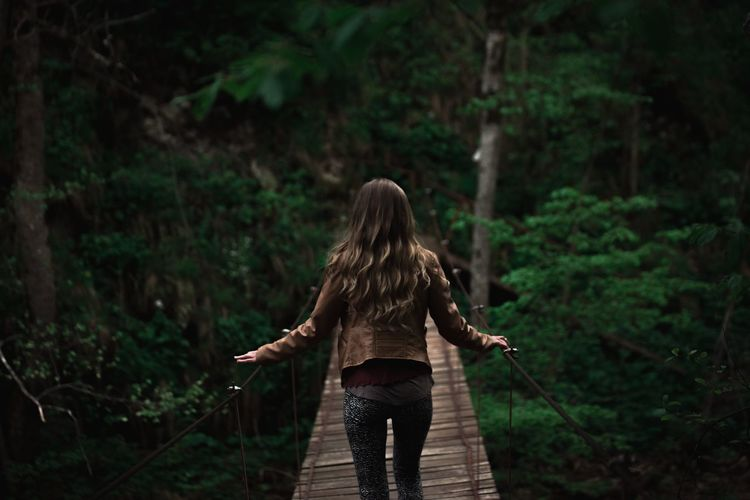 Rear view of woman on bridge in a forest