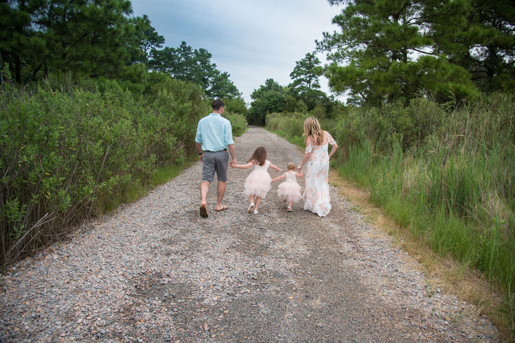 Rear view of family walking on dirt road amidst forest