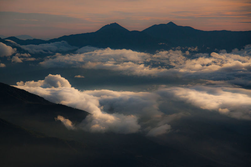 Scenic view of cloudscape against mountains during sunset