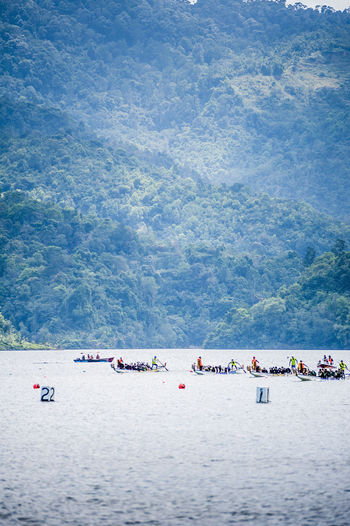 People rowing boats in river at dragon boat festival