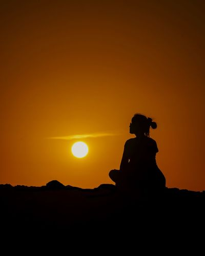 Silhouette man sitting against orange sky during sunset
