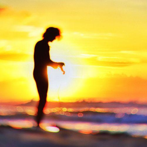 Silhouette woman standing in sea against orange sky