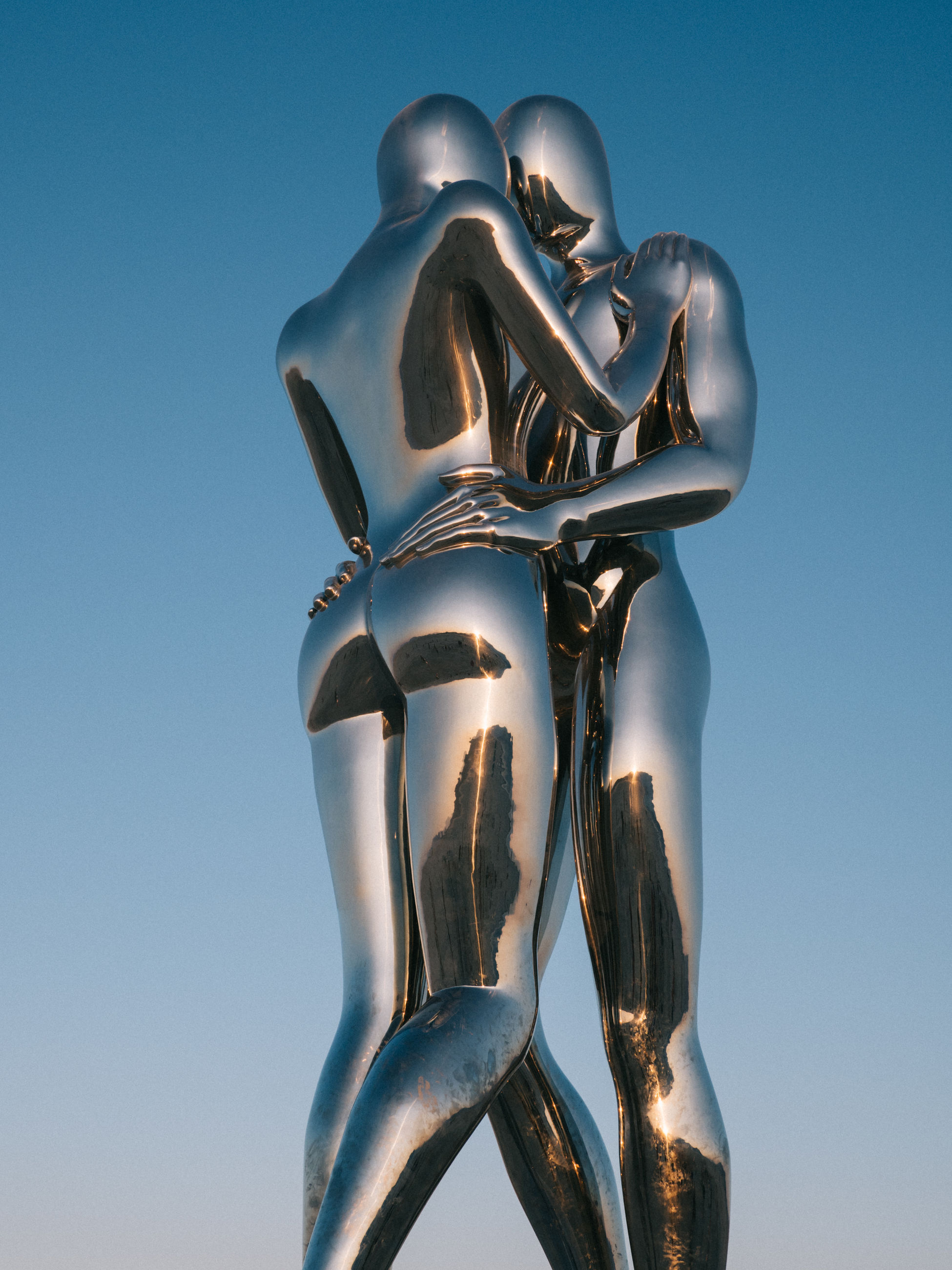 no people, clear sky, low angle view, human representation, sky, representation, metal, blue, sculpture, art and craft, creativity, nature, male likeness, gold colored, female likeness, close-up, statue, craft, day, sunlight, silver colored, blue background