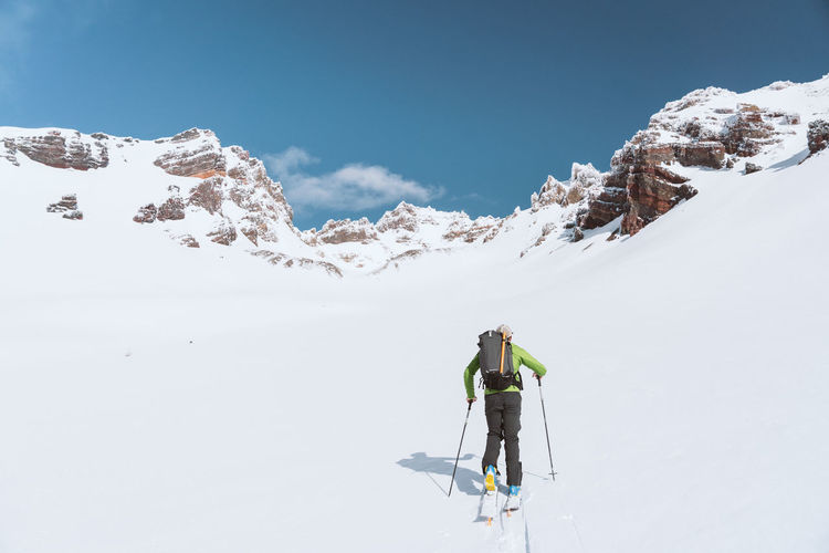 Person skiing on snowcapped mountain against sky