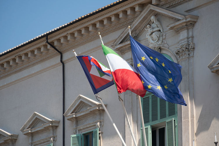 European and italian flags and italian presidential pennant outside quirinale palace, rome