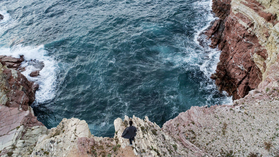 High angle view of man walking on rock against sea