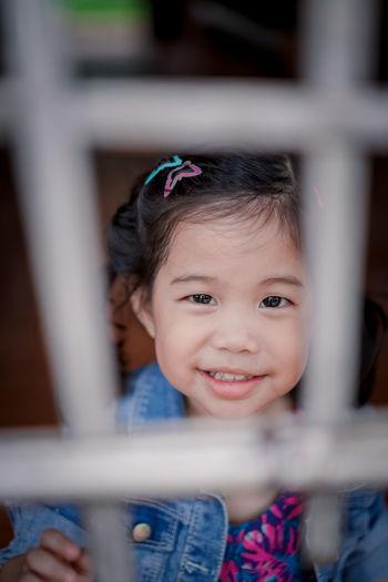 Portrait Of Cute Girl Seen Through Fence