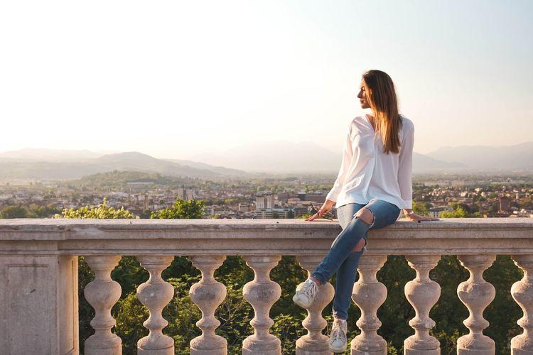 Woman sitting on balustrade against landscape