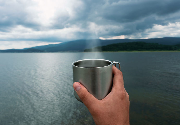 Midsection of person holding drinking water against lake
