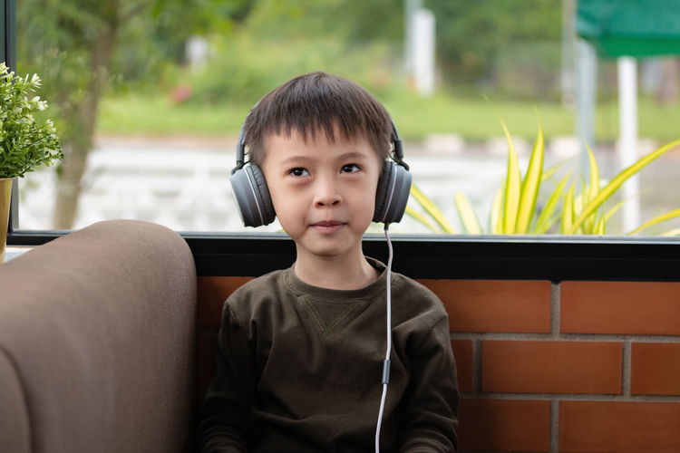 Portrait of boy wearing headphones while sitting against brick wall