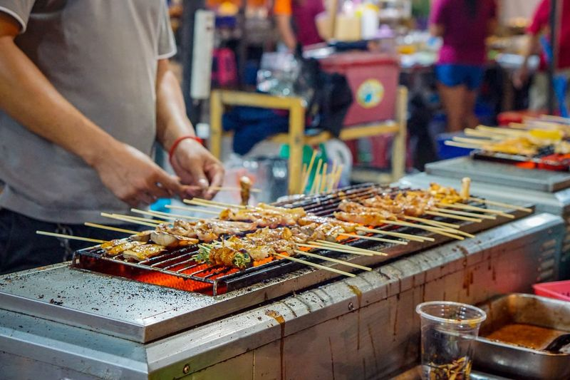 Man preparing food on barbecue grill at market