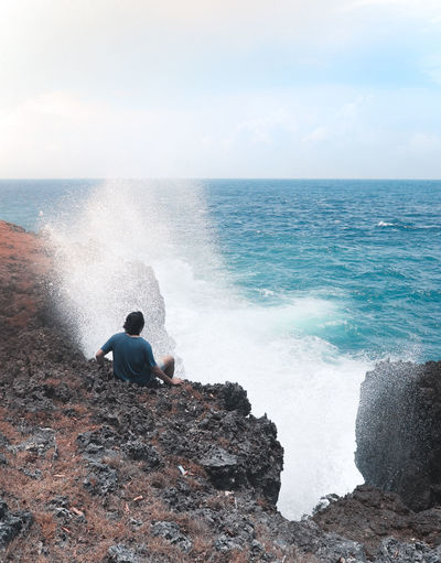 Rear view of man looking at sea while sitting on rock