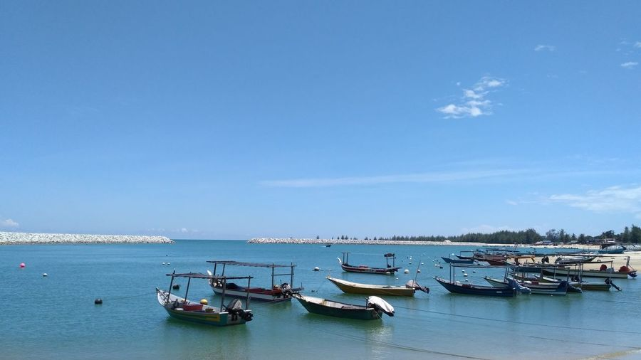Sailboats moored in sea against blue sky