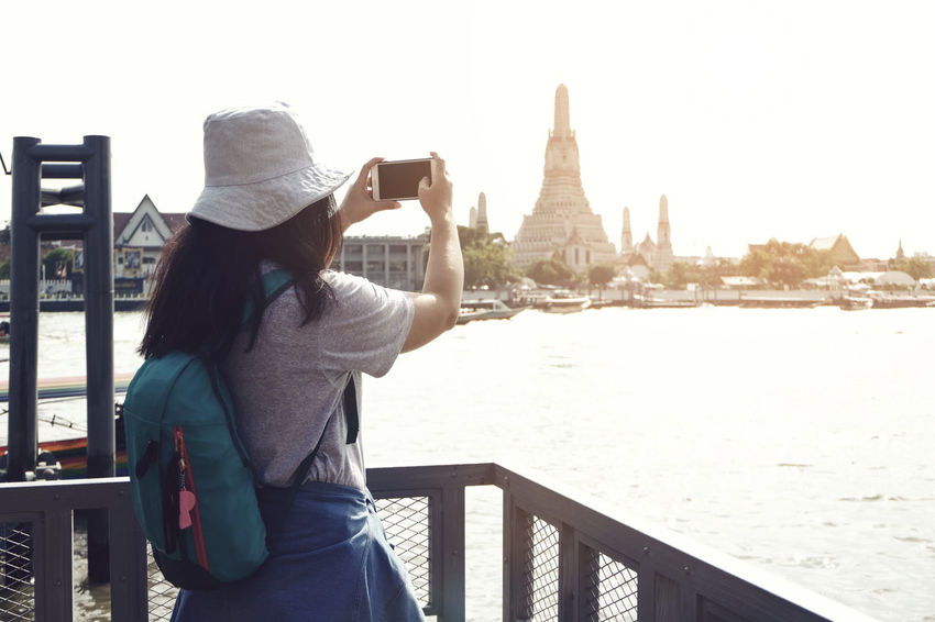 woman travel by boat at Bangkok Thailand Arun Arun Temple Bangkok Thailand Architecture Building Exterior Lifestyles Mobile Phone Nature One Person Outdoors Photography Themes Real People Sky Smart Phone Standing Temple Water Women