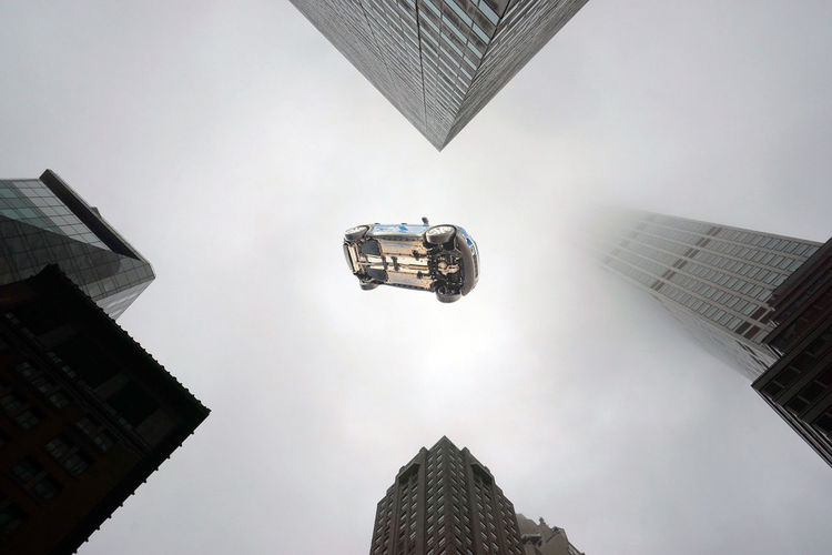 A flying car above the buildings and skyscrapers in New York city in a foggy day Building Exterior Architecture Built Structure Building Low Angle View City Sky Tall - High Skyscraper Office Building Exterior Travel Directly Below No People Office Flying Car Flying Car Transportation Futuristic Fantasy Abstract Business Insurance Finance Amazing
