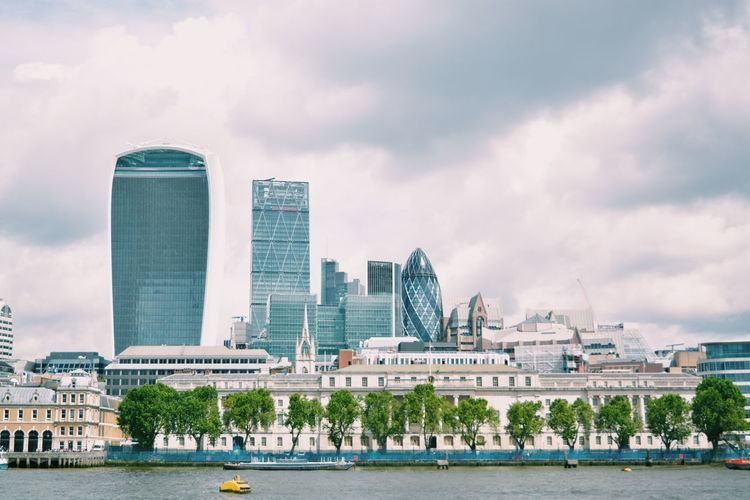 Cityscape by thames river against cloudy sky