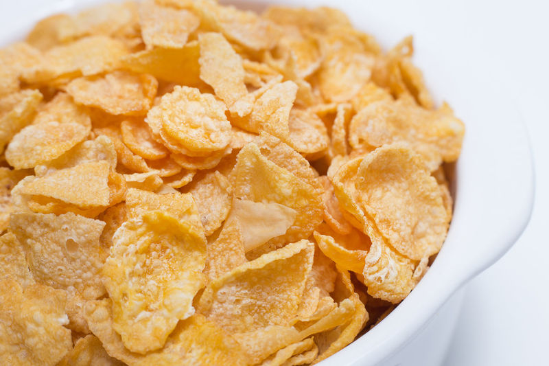 The image Close up Cornflakes cereal breakfast in white bowl on white background. CornflakesCrew Bowl Close-up Cornflakes Cornflakes & Coffee Flavors Cornflakes And Milk Crunchy Day Food Food And Drink Freshness Heap Indoors  No People Potato Chip Ready-to-eat Snack Studio Shot Unhealthy Eating