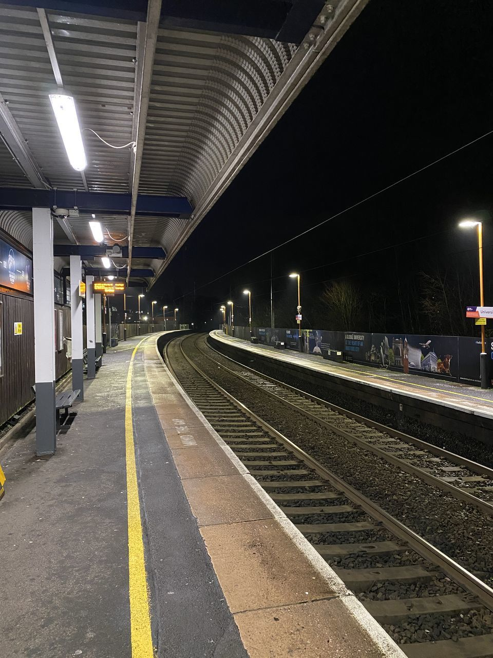 VIEW OF RAILROAD STATION PLATFORM AT RAILWAY TRACKS