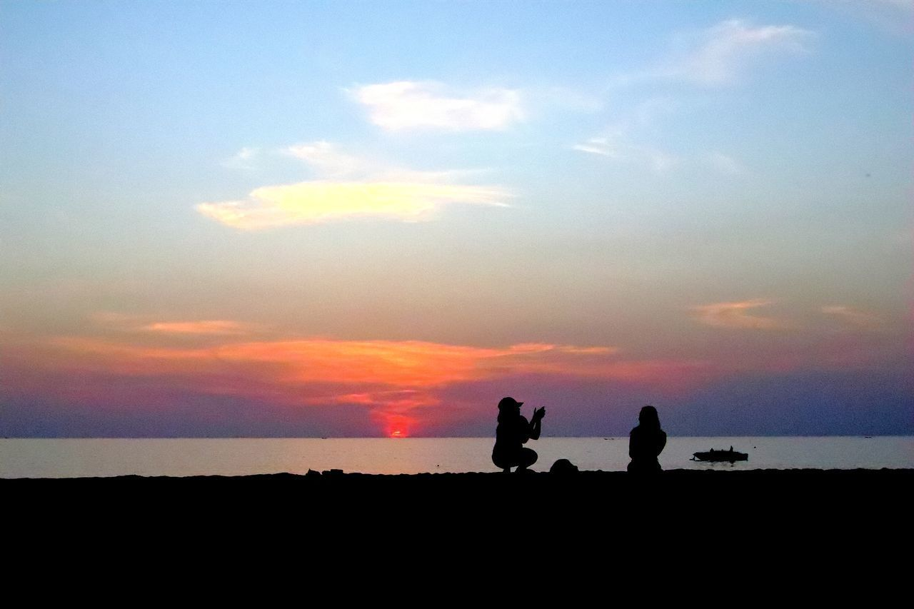SILHOUETTE MEN STANDING ON LAND DURING SUNSET