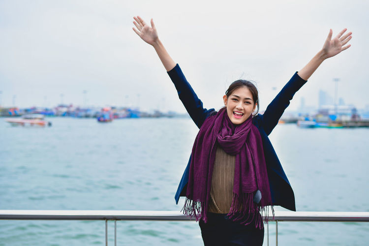 Portrait of cheerful woman standing with arms raised by sea against clear sky
