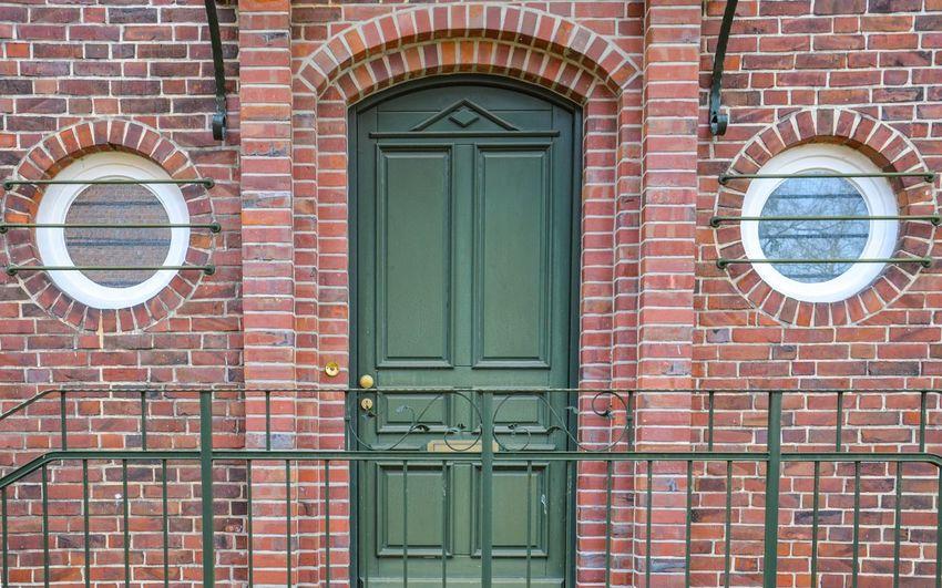 Closed green door on brick wall