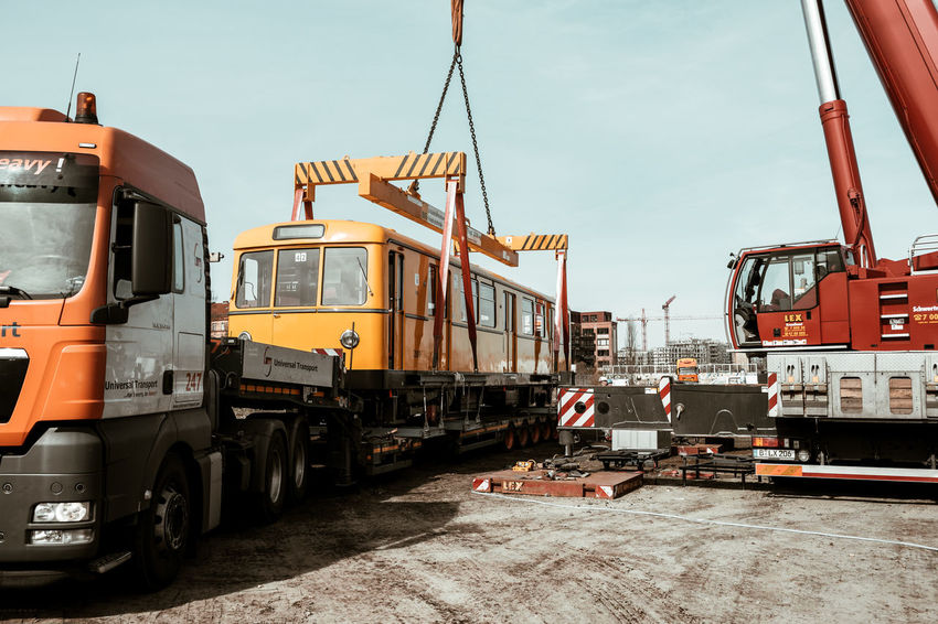 Old subway train on a lorry Berlin Photography Berliner Ansichten Business Commercial Land Vehicle Construction Machinery Day Freight Transportation Harbor Industrial Building  Industry Land Vehicle Mode Of Transport No People Outdoors Shipping  Sky Subway Train Train - Vehicle Transportation Truck