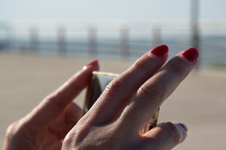 Cropped Hands Of Woman Holding Mobile Phone In Sunny Day